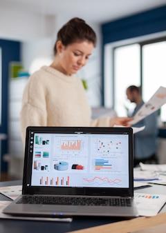 Computer portatile con grafici finanziari sull'ufficio della start up company. imprenditore esecutivo, manager leader in piedi lavorando su progetti con diversi colleghi. imprenditore professionale aziendale di successo