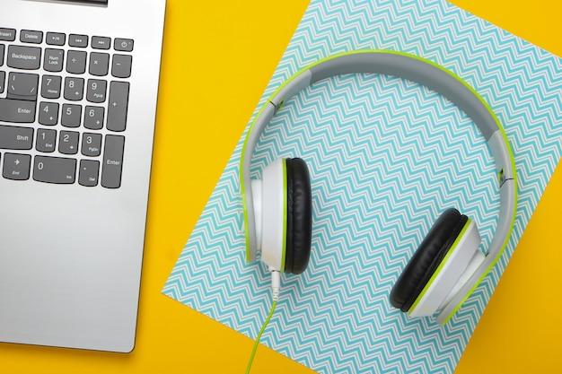 Computer portatile con le cuffie sulla superficie gialla blu