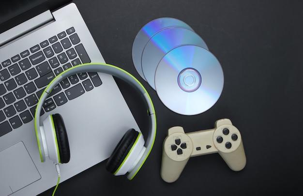 Computer portatile con cuffie, gamepad, dischi cd sulla superficie nera