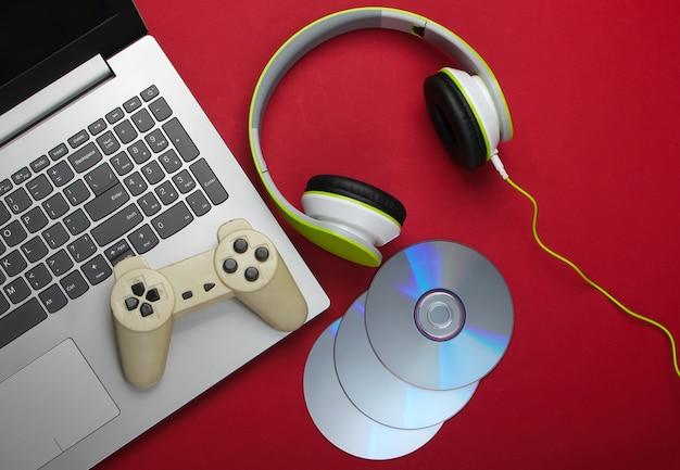 Computer portatile con cuffie, gamepad, dischi cd sulla superficie rossa