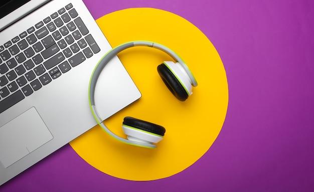 Computer portatile con cuffie sulla superficie viola con cerchio giallo