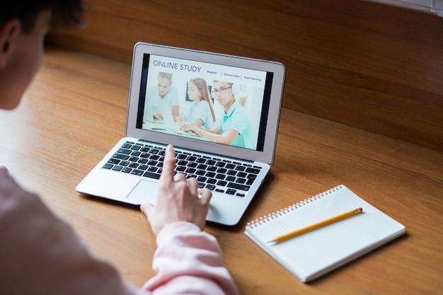 Computer portatile con l'immagine di scolari sullo schermo e studente di college toccando il pulsante della tastiera durante la navigazione in rete