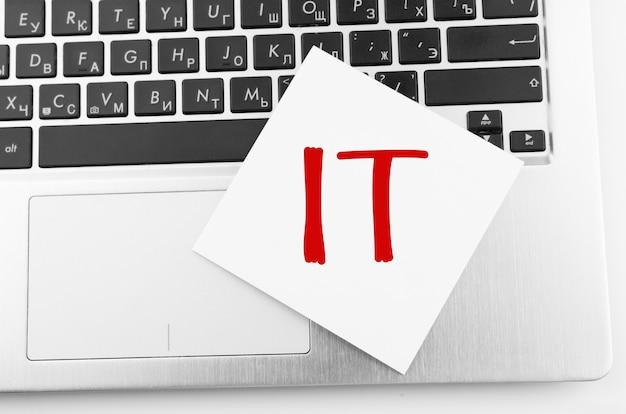 Computer portatile con memo stick sulla tastiera con testo it su di esso