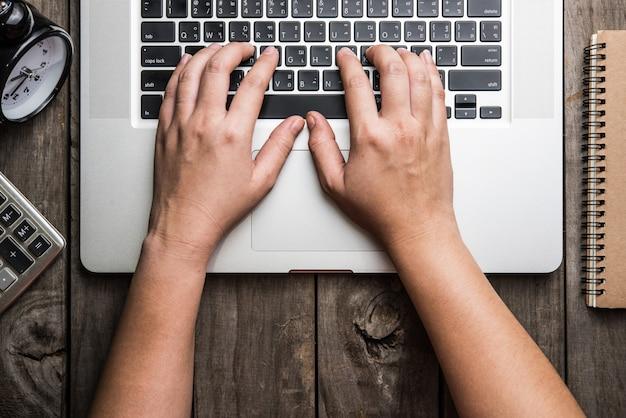 Computer portatile con blocco note e orologio con sulla vecchia tavola di legno.