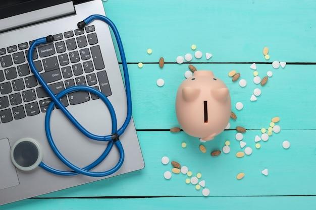 Computer portatile con salvadanaio, bottiglia di pillole, stetoscopio su una superficie blu. acquista medicine online. dottore in linea. vista dall'alto