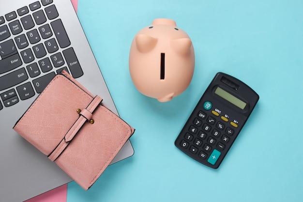Computer portatile con salvadanaio, calcolatrice e portafoglio su pastello blu rosa