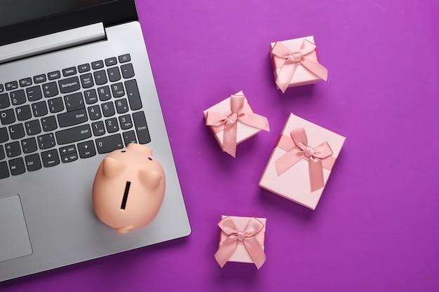 Computer portatile con salvadanaio e scatole regalo su viola