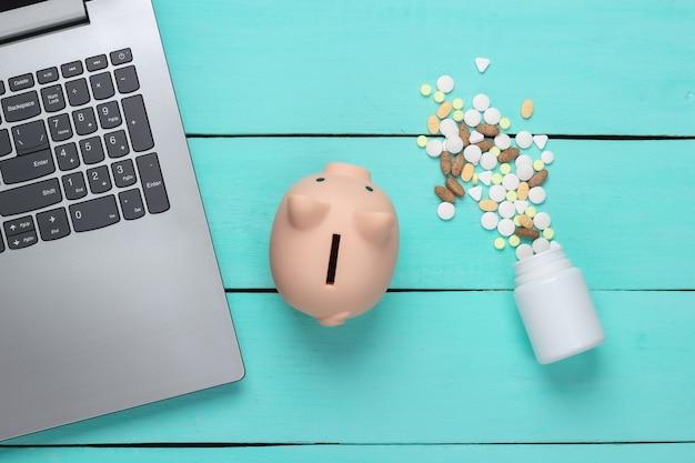 Computer portatile con salvadanaio, bottiglia di pillola su una superficie blu. acquista medicine online. vista dall'alto