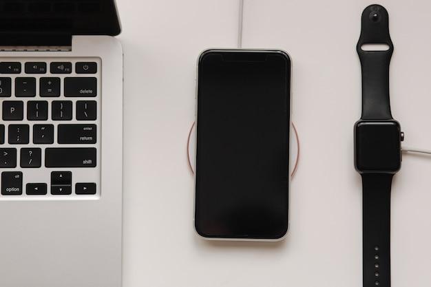 Computer portatile con orologio intelligente e telefono in carica tramite caricabatterie wireless. vista dall'alto. posto per il testo.
