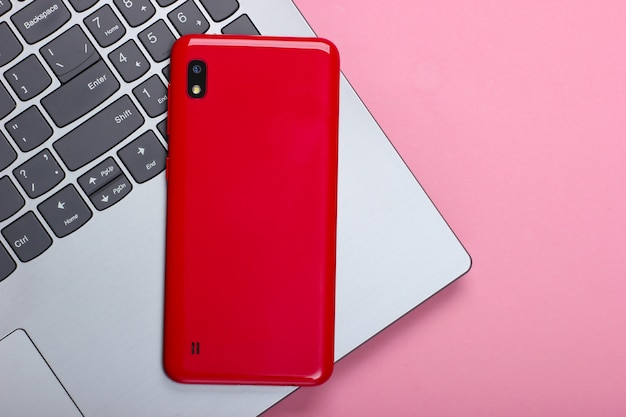 Computer portatile con smartphone su un pastello rosa