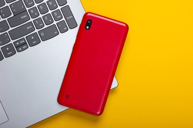 Computer portatile con smartphone su un colore giallo