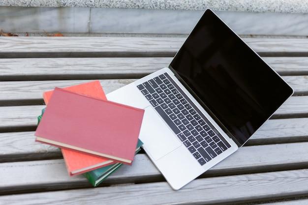 Computer portatile con una pila di libri su una panchina