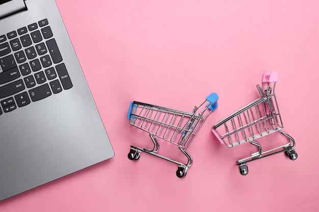 Computer portatile con carrelli per supermercati su un pastello rosa