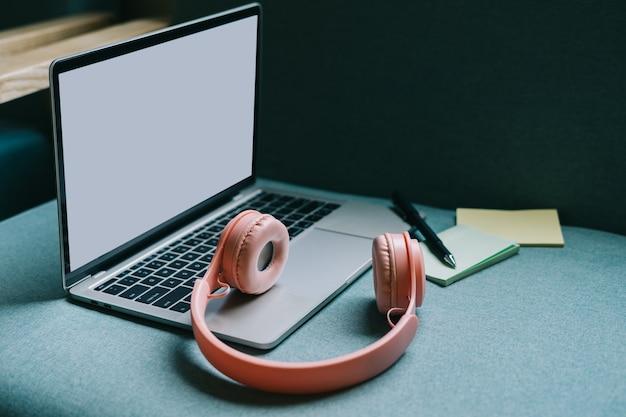 Portatile con schermo bianco e cuffie rosa accanto