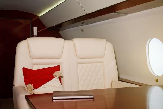 Computer portatile sul tavolo da lavoro di interni di lusso in jet privato. aereo d'affari moderno e confortevole con decorazioni. concetto di qualità del servizio passeggeri nell'industria aeronautica, al massimo