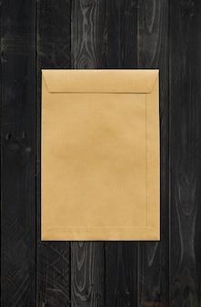 Modello di mockup di enveloppe di carta marrone grande a4 isolato su fondo di legno nero
