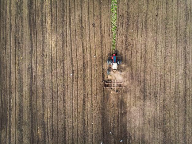 Una grande macchina agricola coltiva la terra. la vista dall'alto. arare il terreno per piantare colture. foto dalla vista a volo d'uccello con un quadrirotore