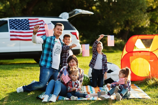 Grande famiglia americana che trascorre del tempo insieme. con le bandiere degli stati uniti contro la grande auto suv all'aperto. vacanze americane. quattro bambini.