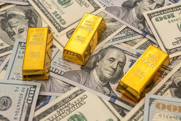 Grandi lingotti d'oro della banca su banconote in dollari. concetto di risparmio