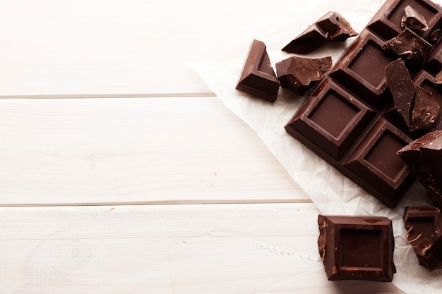 Una grande barra di cioccolato nero su un fondo di legno bianco con spazio per testo.