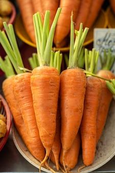 Carota arancione grande, bella, succosa e dolce con una corta coda verde in un piatto bianco.