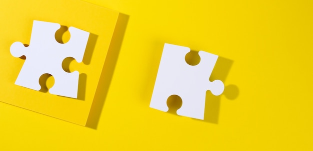Grande puzzle di carta bianca vuota con ombra su sfondo giallo, vista dall'alto. sfondo creativo astratto per designer, distesi piatti