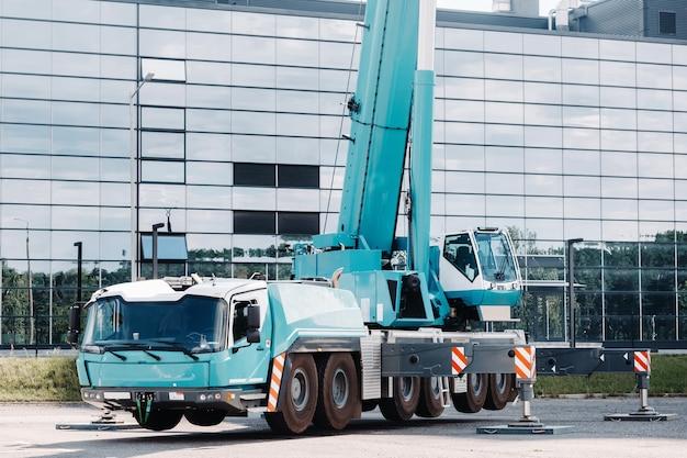 Una grande gru da camion blu è pronta per operare su supporti idraulici su una piattaforma accanto a un grande edificio moderno.