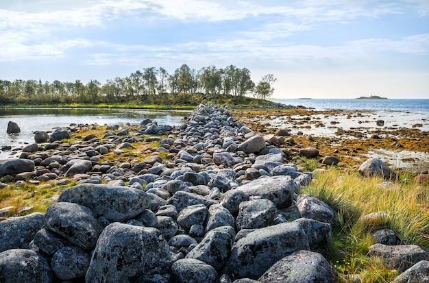 Grandi massi nelle gabbie filippovsky sulle isole solovetsky tra l'erba verde e l'acqua blu del mar bianco
