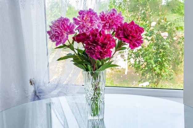 Un grande mazzo di peonie fiori rosa in piedi nella stanza sul tavolo in un vaso di cristallo vicino alla finestra