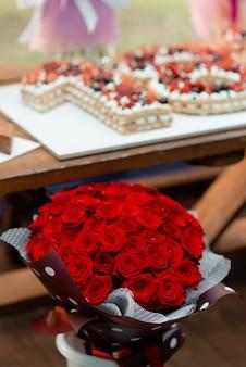 Un grande mazzo di rose rosse sullo sfondo di una torta festiva con una torta.