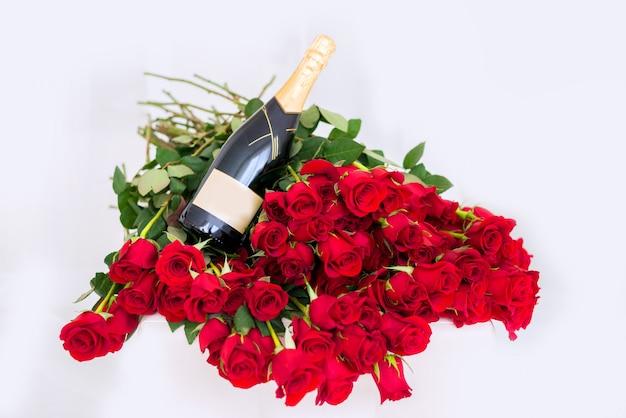 Grande mazzo di rose rosse con una bottiglia di champagne.