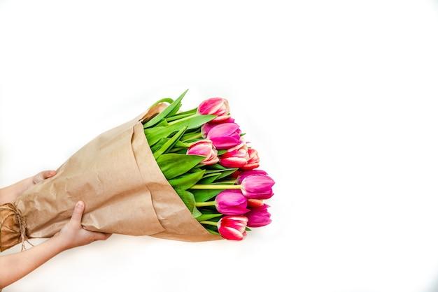 Grande mazzo di tulipani in mano su uno sfondo bianco closeup concept per l'8 marzo