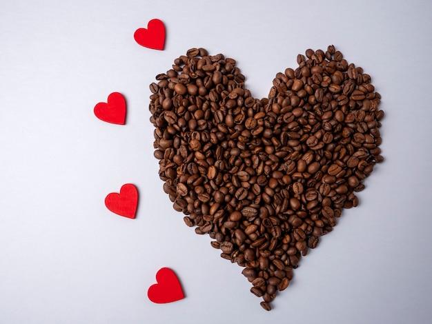 Un grande cuore marrone fatto con i chicchi di caffè si trova accanto a quattro cuori rossi