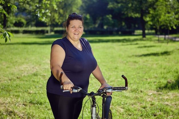 Una donna caucasica di grande corporatura va in bicicletta nel parco in una soleggiata giornata estiva