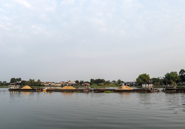 La grande barca da carico che carica molta sabbia sta navigando lungo il grande fiume per il trasporto al cantiere vicino a bangkok in thailandia, vista frontale per lo spazio della copia.