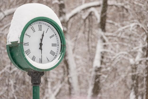 Grande orologio con uno spesso strato di neve nel parco sullo sfondo degli alberi