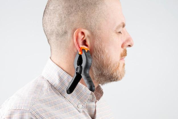 Grande molletta da bucato appesa all'orecchio di un uomo barbuto