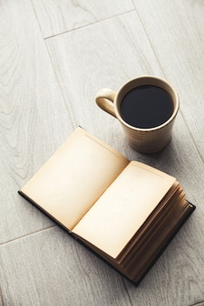 Grande tazza di caffè e libro aperto. istruzione, hobby, bevande.