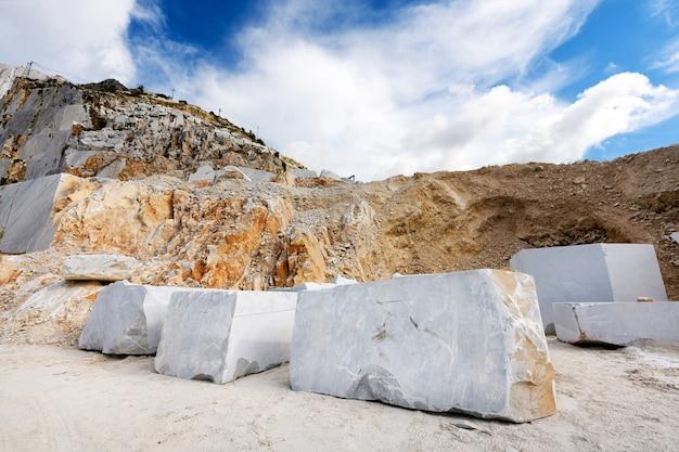 Grandi blocchi tagliati di marmo bianco di carrara in una miniera o cava a cielo aperto in toscana, italia in attesa di trasporto