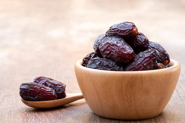 Il grande dattero fruttifica medjool in tazze e cucchiai di legno su un cemento con sfondo sfocato