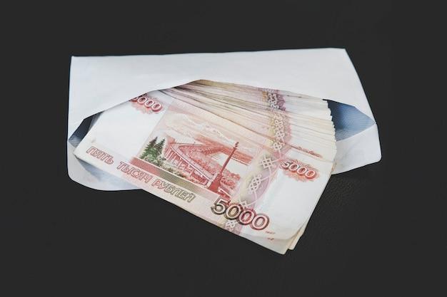Grandi tagli da 5000 rubli in una busta bianca. una mano dell'uomo tiene una busta con soldi. il concetto di concussione e corruzione