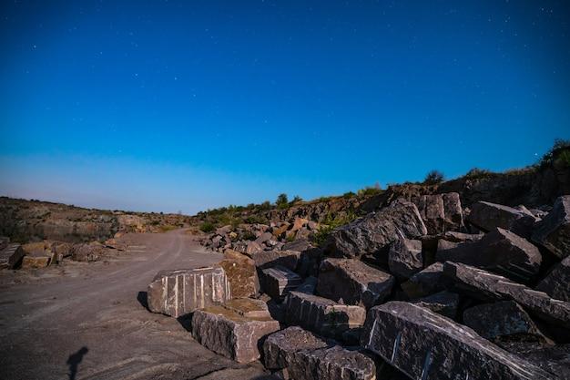Grandi depositi di materiali lapidei nei pressi di una miniera nei carpazi sullo sfondo del cielo con la luna