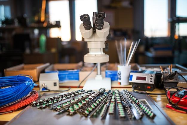 Il grande microscopio elettronico e il pannello di indicatori luminosi a led sono impilati su una piastra per prepararsi alla ricerca di componenti elettronici in un laboratorio