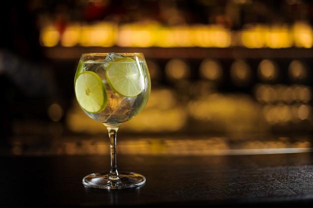 Ampio ed elegante bicchiere da cocktail con cocktail fresco aspro e dolce con fettine di lime