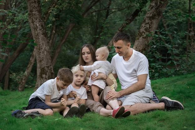La famiglia numerosa ha un picnic all'aperto. grande divertimento e famiglia felice.