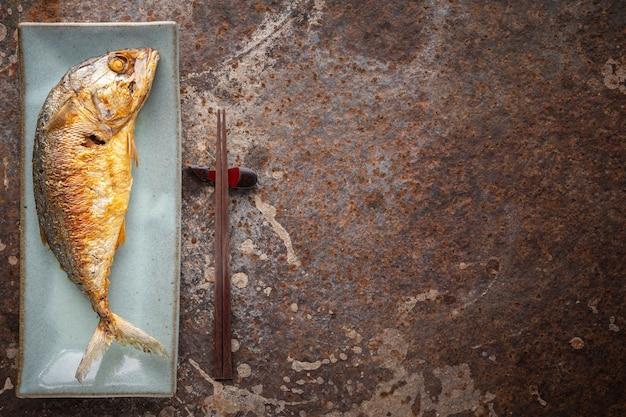Grande sgombro fritto in un piatto di ceramica rettangolare accanto alle bacchette su uno sfondo arrugginito con copia spazio per il testo, vista dall'alto