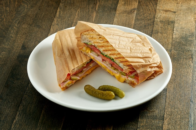 Grande panino fritto con prosciutto, pomodori, sottaceti e formaggio fuso, servito in pergamena sul piatto bianco sulla tavola di legno