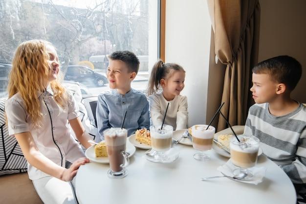 Una grande compagnia amichevole di bambini celebra la vacanza in un caffè con un delizioso dessert. il giorno della nascita