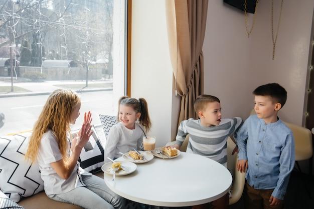 Una grande compagnia amichevole di bambini celebra la vacanza in un caffè con un delizioso dessert.