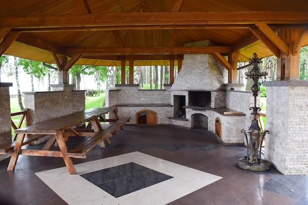 Ampio gazebo nel parco con tetto in legno e pavimento in mosaico di pietra. all'interno c'è un tavolo in legno